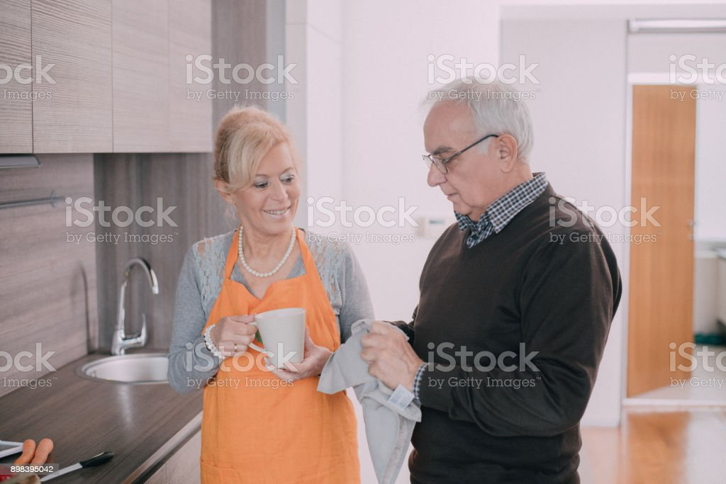 Senior couple standing in the kitchen and wiping wet dishes stock photo