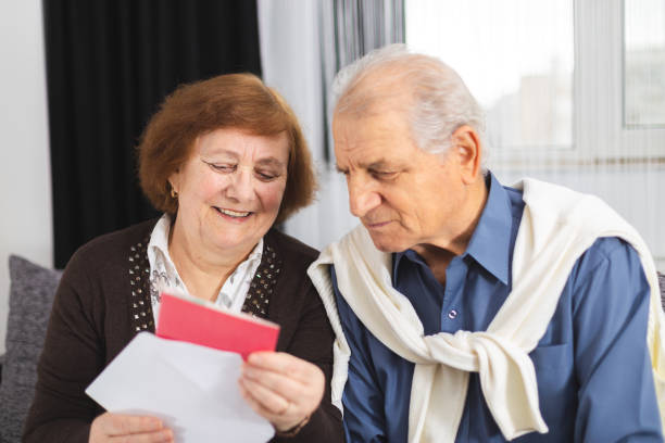 Senior couple standing on the couch and reading a letter received. Portrait Of A Happy Senior Couple At Home Reading Paper stock photo