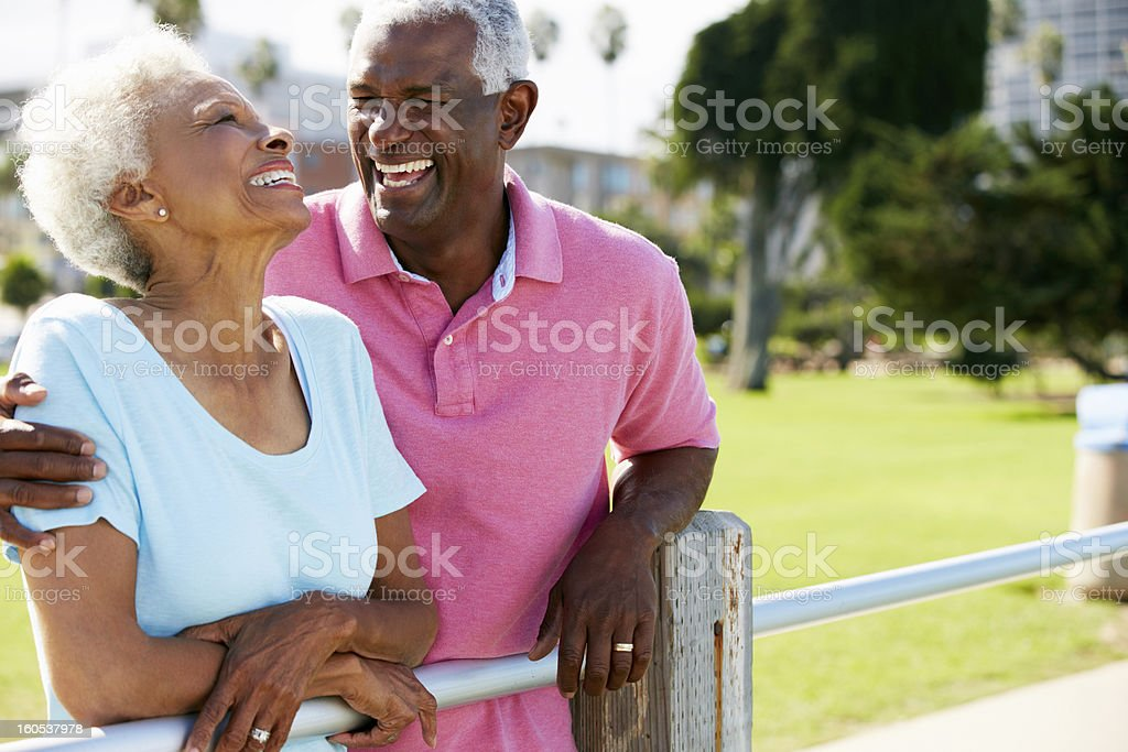 Senior couple standing together at a fence post stock photo