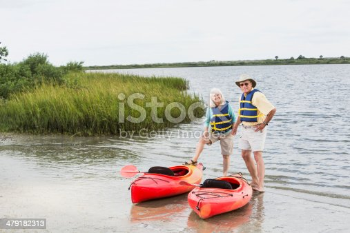 istock Senior couple standing with kayaks by water 479182313