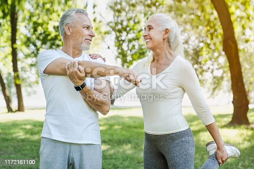 942580016istockphoto Senior couple stretching in park outdoors before yoga and fitness exercises while looking on each other 1172161100