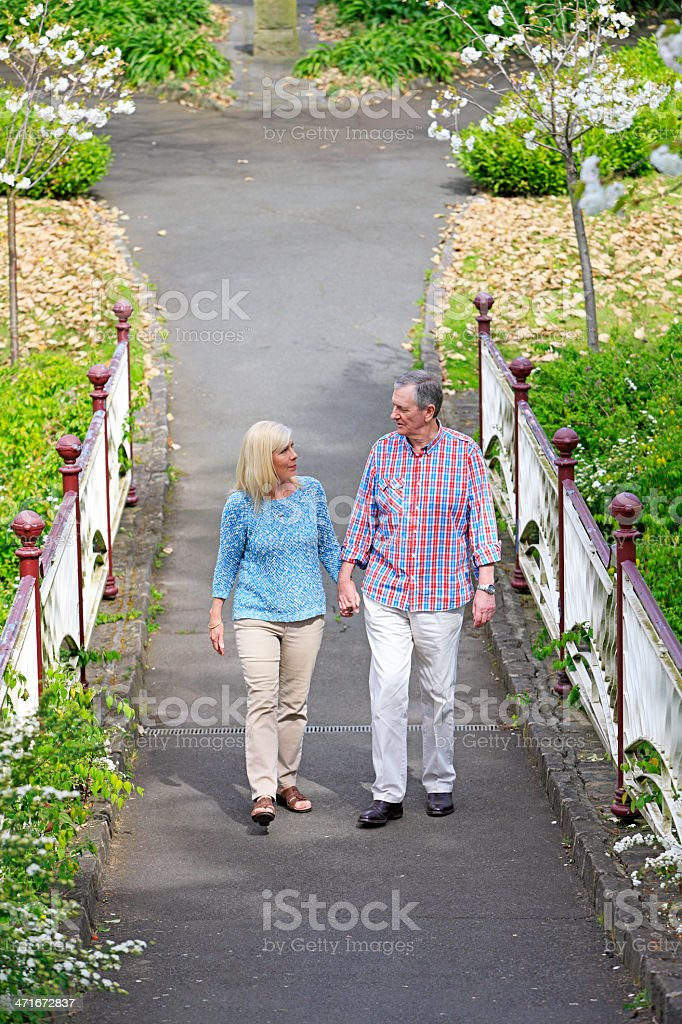 Senior couple strolling hand-in-hand on garden path royalty-free stock photo