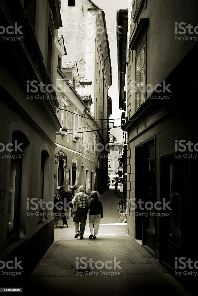 Senior couple strolling in an european alley royalty-free stock photo