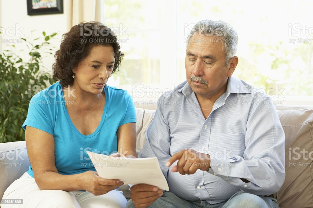 Senior Couple Studying Financial Document At Home royalty-free stock photo