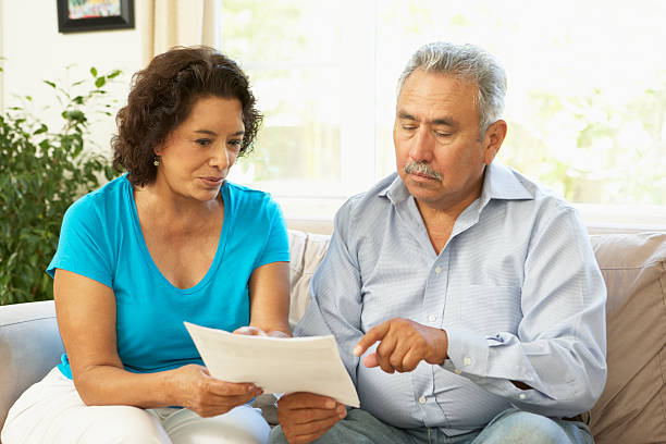 Senior Couple Studying Financial Document At Home stock photo