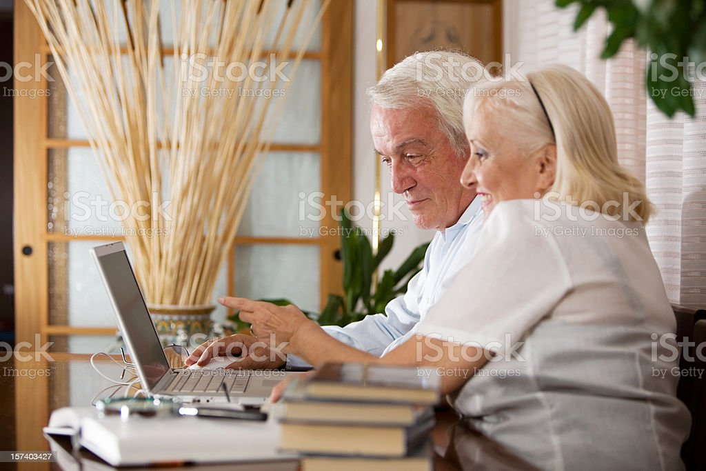 Senior couple surfing together the internet on a laptop royalty-free stock photo