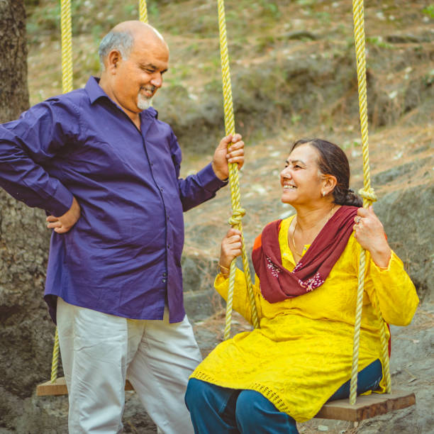 Senior couple swings in their summer vacation. stock photo