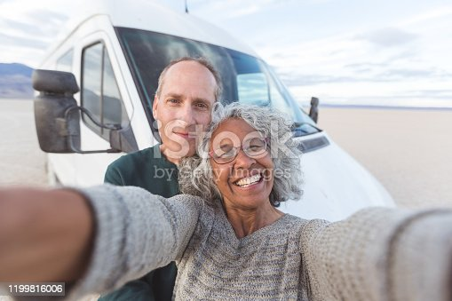 An adorable mixed-race senior couple take a selfie to chronicle their travel adventures in a van across the Oregon desert. They are standing in front of their camper van parked in the desert.