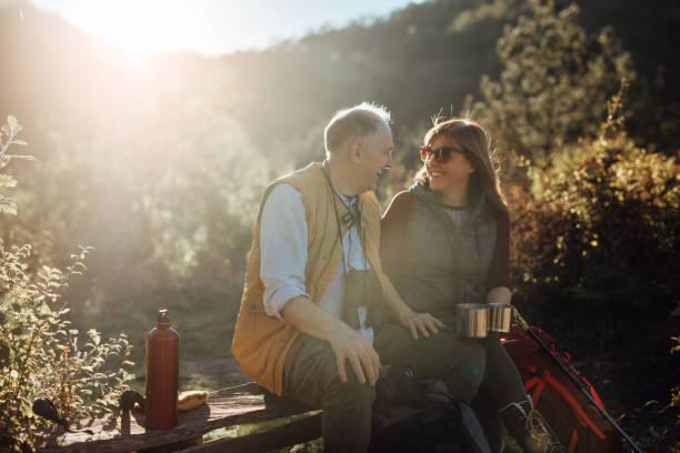 Senior couple taking break from hiking stock photo