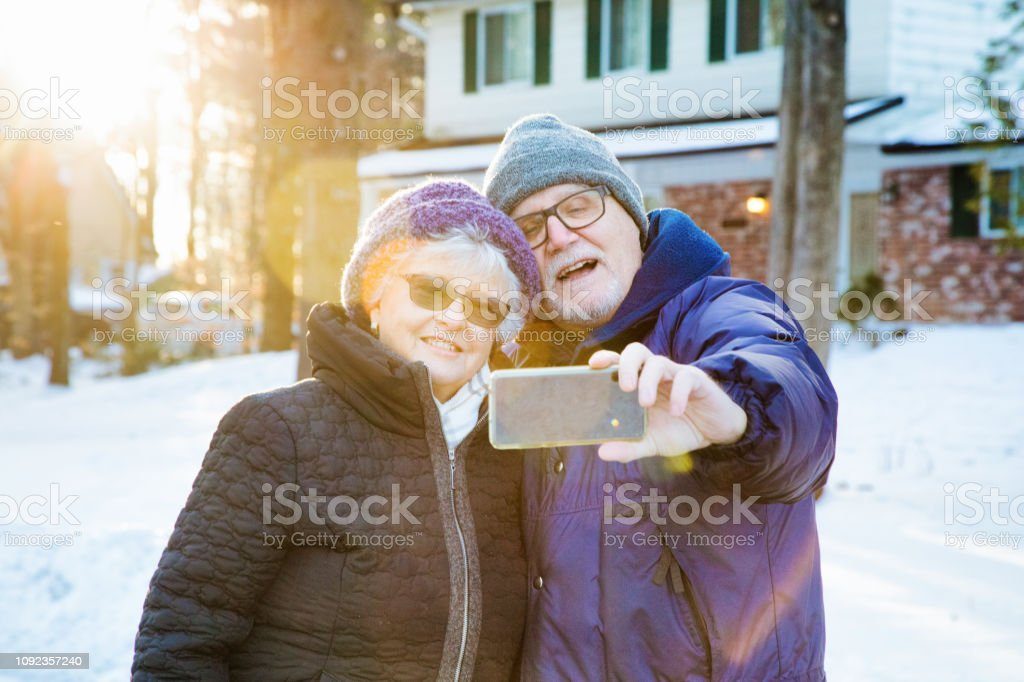 Senior couple taking selfie photograph with mobile phone during a...