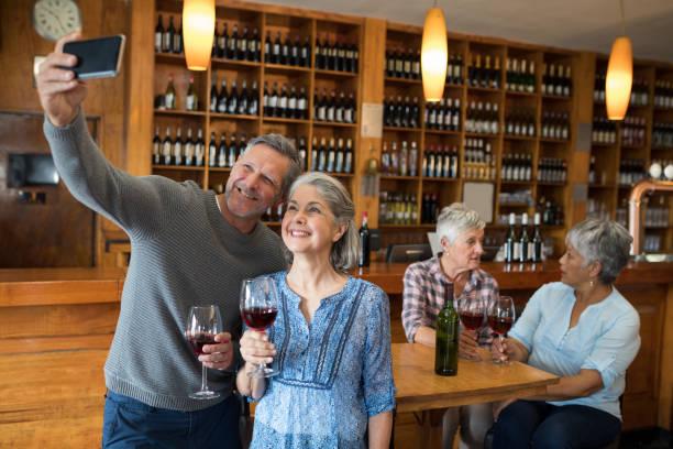 Senior couple taking selfie with mobile phone in restaurant stock photo