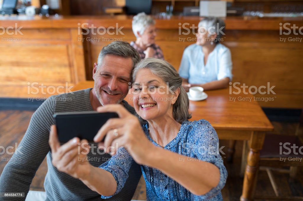 Senior couple taking selfie with mobile phone in restaurant stock photo