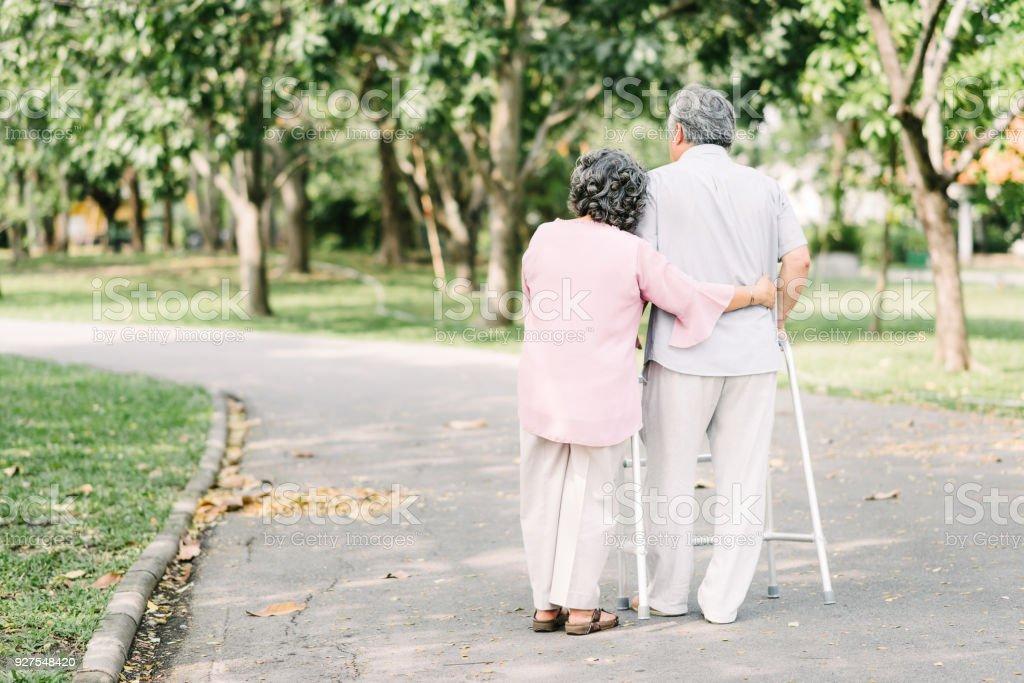 Senior couple talking a walk with walker stock photo