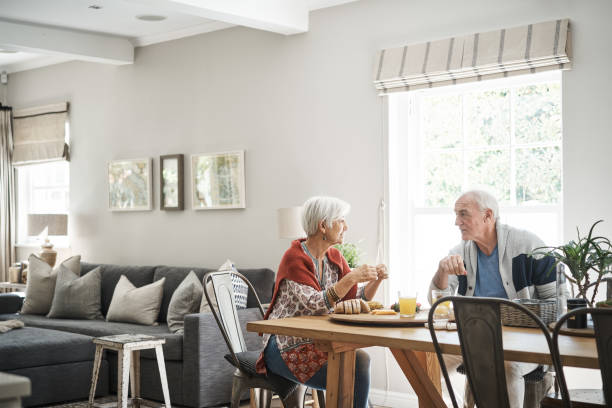 Senior couple talking together over breakfast in the morning stock photo