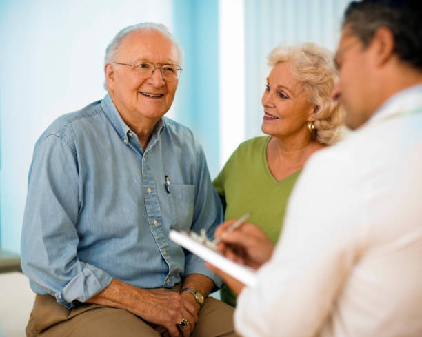 Senior couple talking with doctor. stock photo