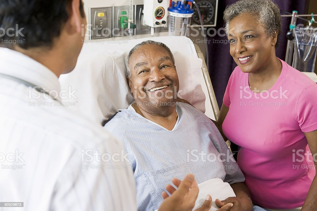 Senior Couple Talking with doctor stock photo