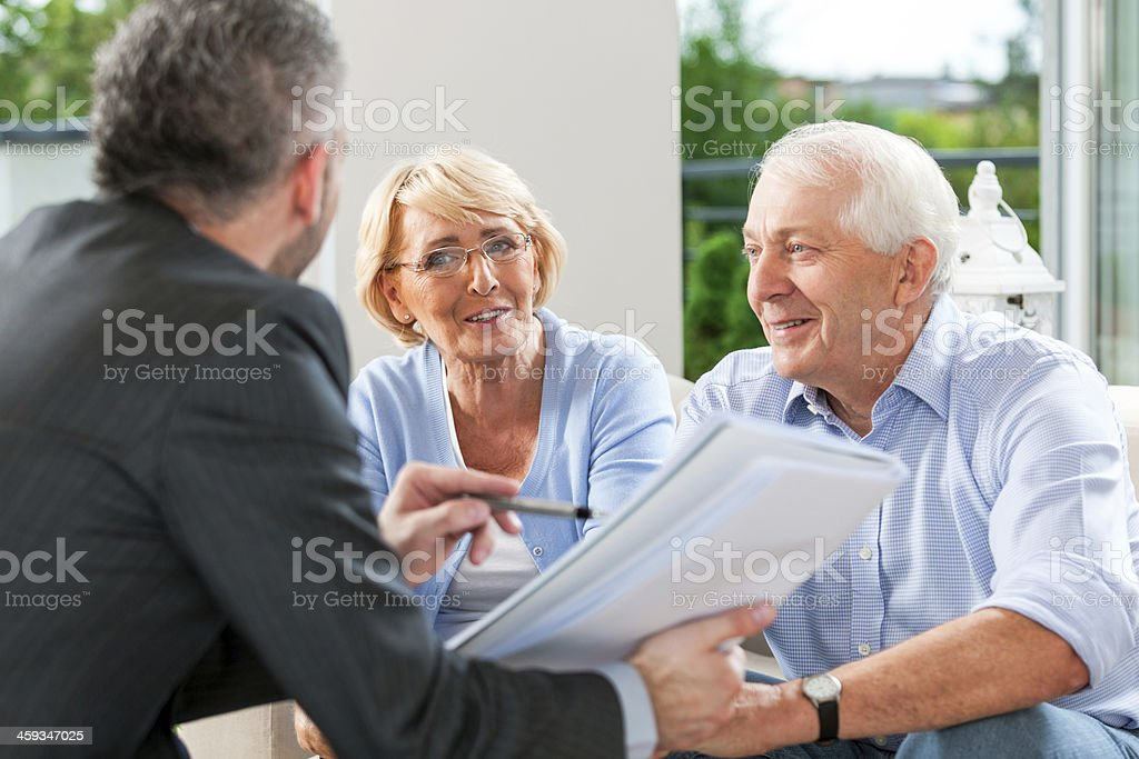 Senior couple talking with financial advisor Cheerful senior couple having meeting with financial advisor or insurance agent at home. Accidents and Disasters Stock Photo
