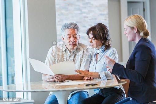 istock Senior couple talking with financial advisor 896461064