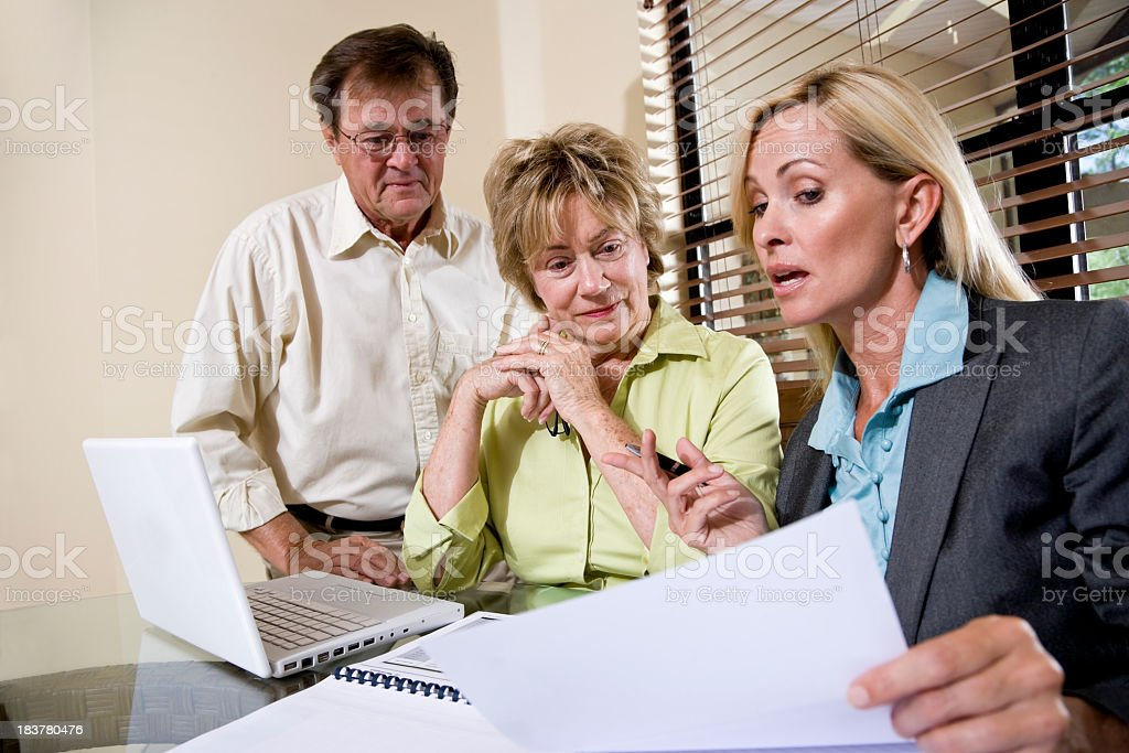 Senior couple talking with financial planner or consultant stock photo