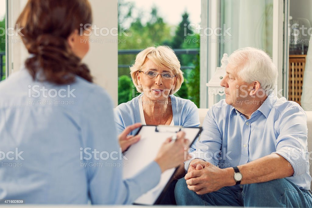Senior couple talking with insurance agent stock photo