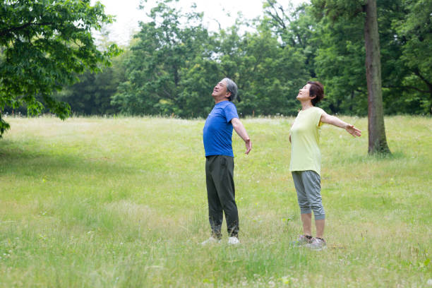 a senior couple to breathe deeply - forest bathing foto e immagini stock