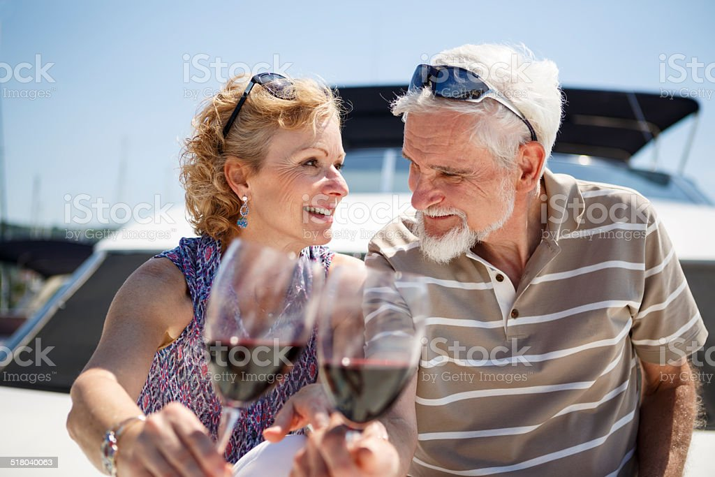 Senior couple toasting each other with wine on yacht stock photo