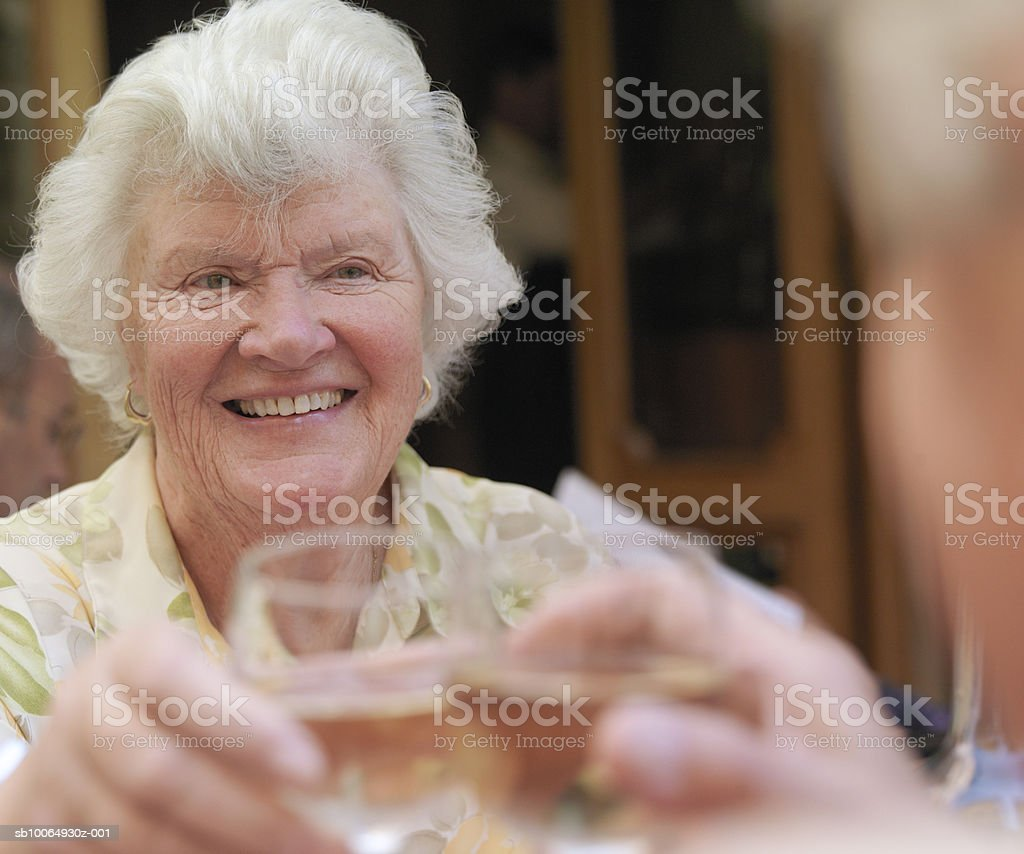 Senior couple toasting wine glasses, focus on woman foto de stock libre de derechos