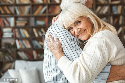 Aged man and woman looking camera smiling together at home in the living room dancing ballroom dance hugging