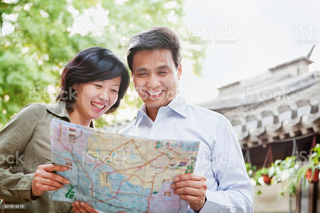 Senior couple tourists looking at map stock photo