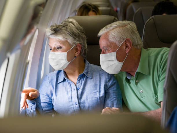 senior couple traveling by plane wearing facemasks - covid flight imagens e fotografias de stock