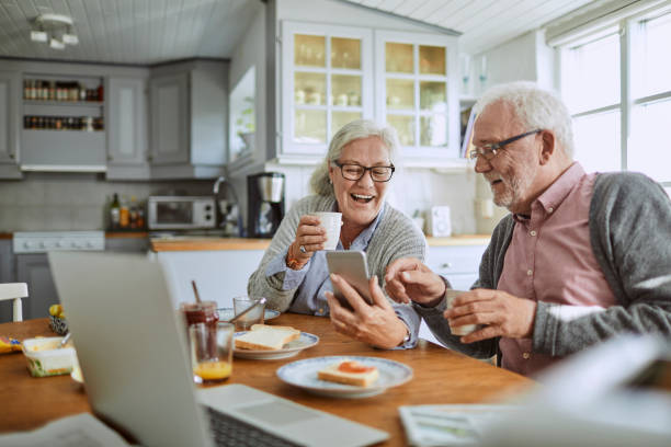 senior couple using a phone - eating technology stock pictures, royalty-free photos & images