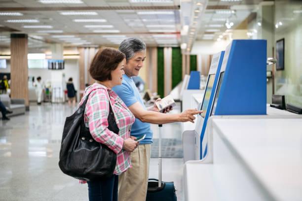 senior-paar mit automatischem check-in-automaten am flughafen - trolley kaufen stock-fotos und bilder