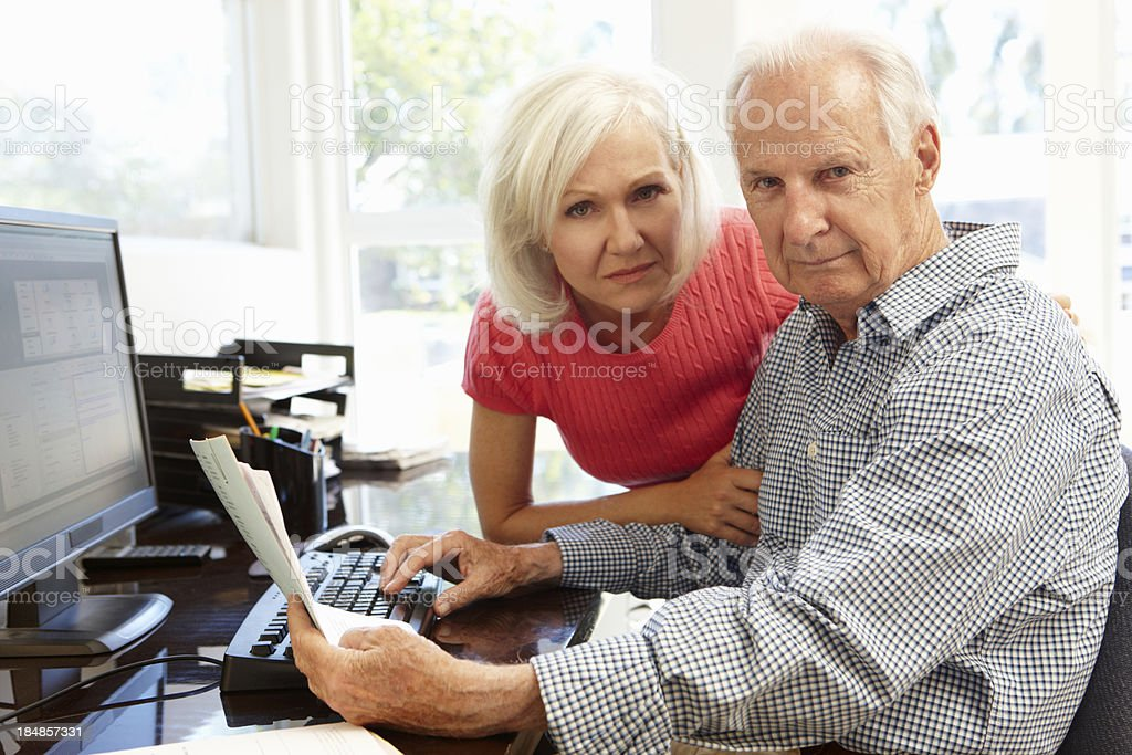 Senior couple using computer at home royalty-free stock photo