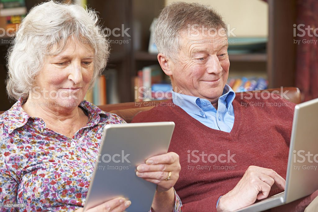 Senior Couple Using Digital Tablet And Laptop At Home stock photo