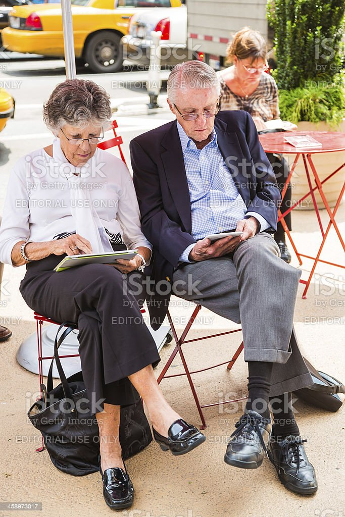 Senior couple using digital tablets, Times Square, New York City royalty-free stock photo