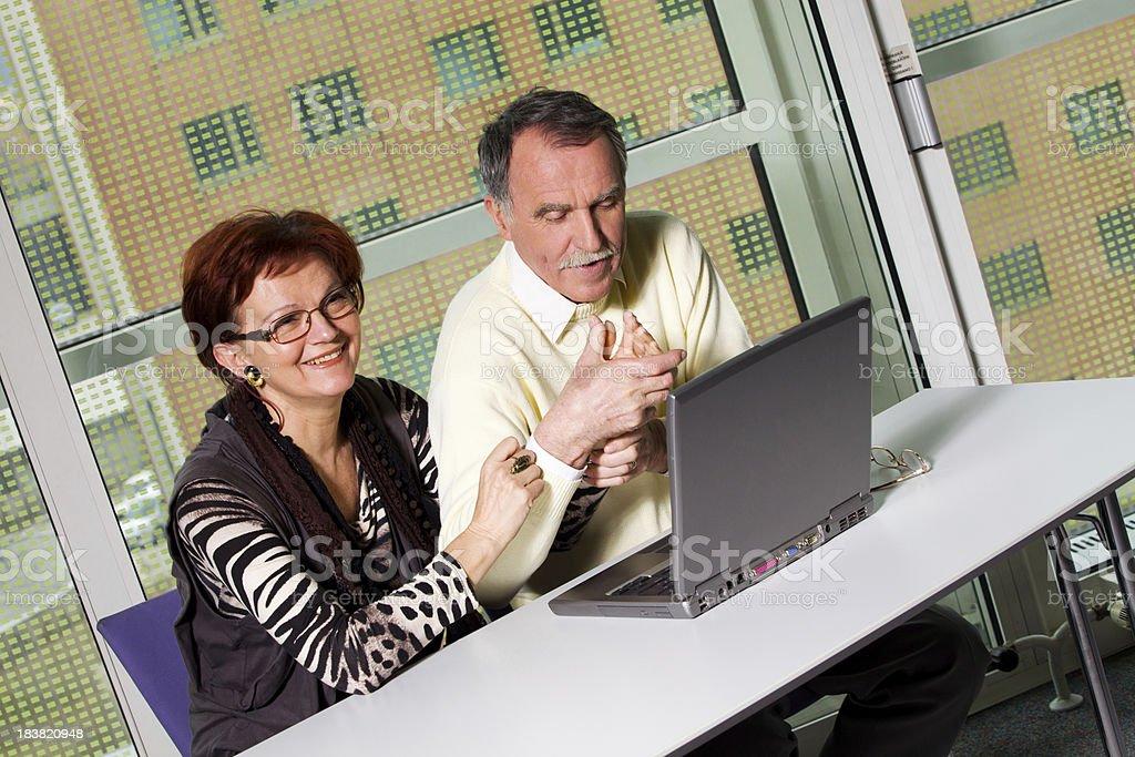 Senior couple using laptop and having fun stock photo