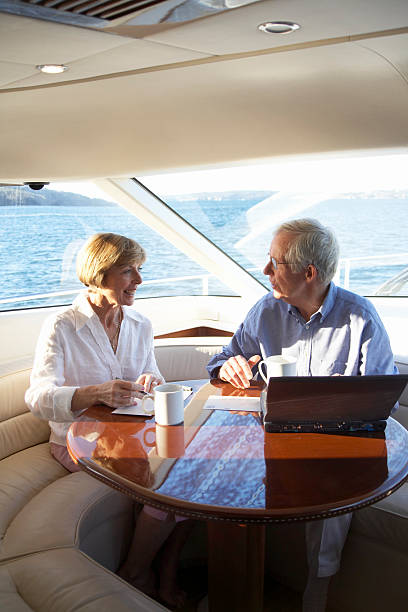 Senior couple using laptop and writing postcards on yacht, smiling stock photo