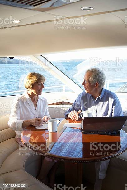 Senior Couple Using Laptop And Writing Postcards On Yacht Smiling Stock Photo - Download Image Now