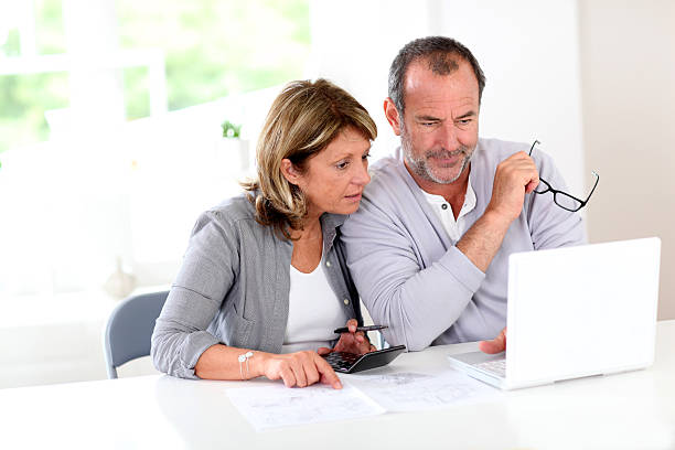 Senior couple using laptop at home stock photo