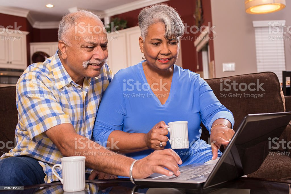 Senior couple using laptop computer at home. stock photo