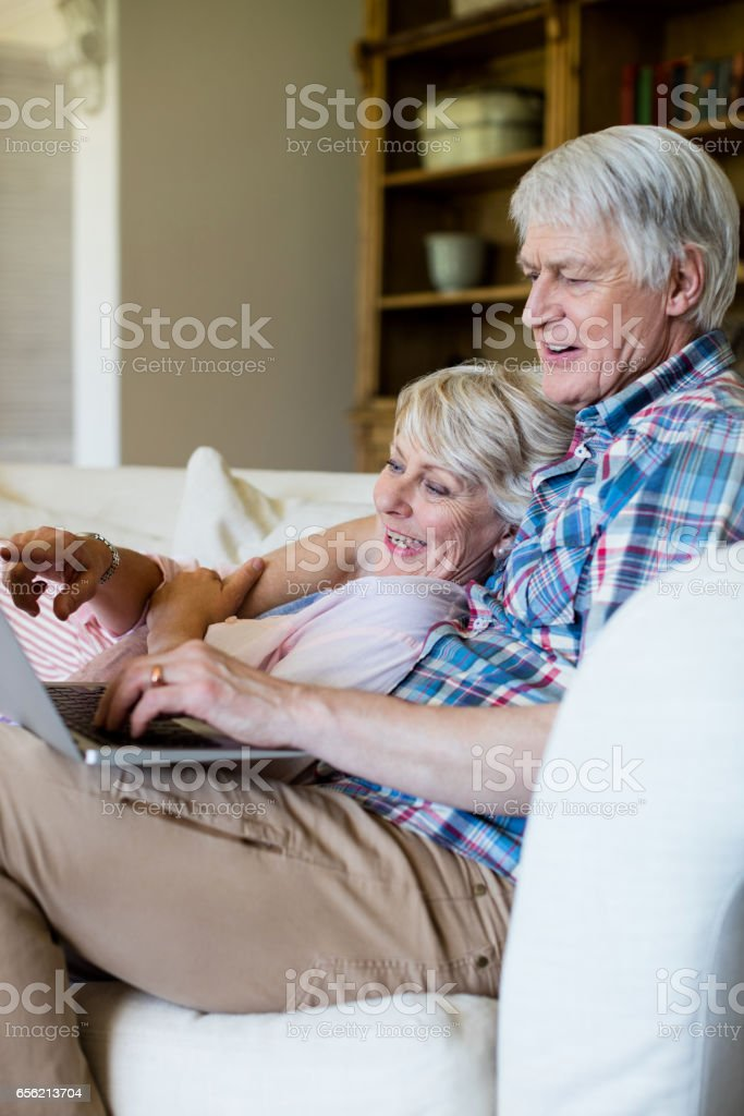 Senior couple using laptop in living room stock photo
