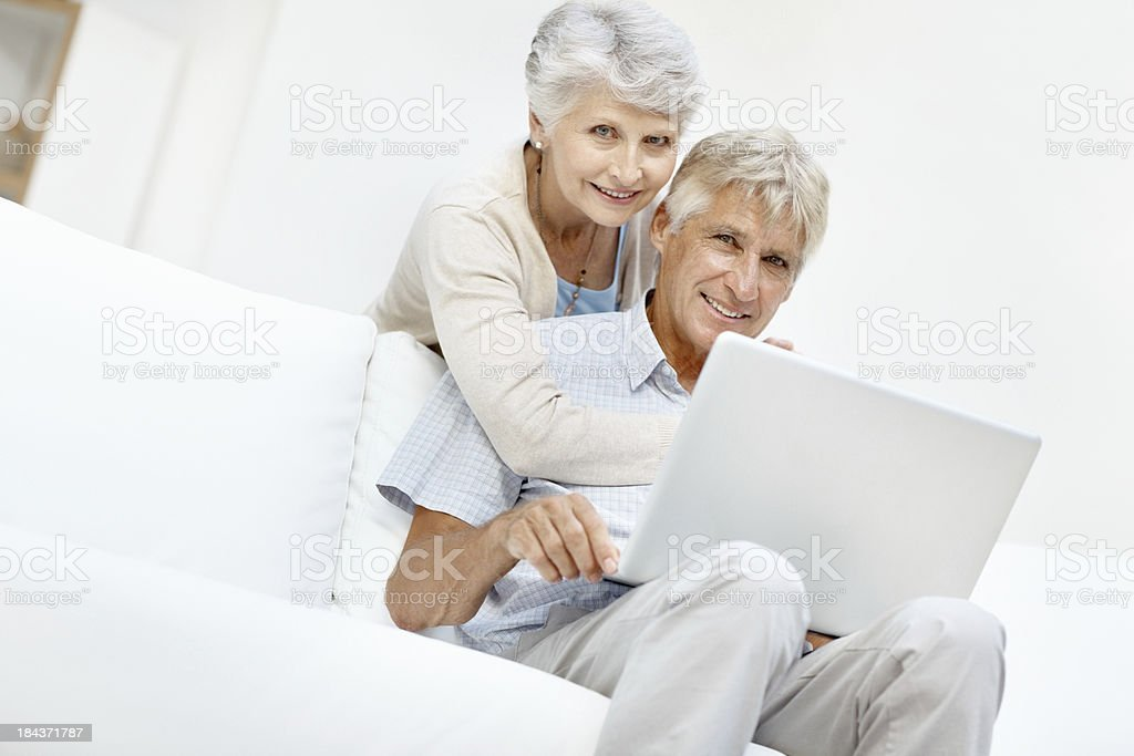 Senior couple using laptop while relaxing at home stock photo