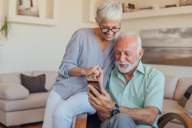 senior paar gebruik mobiele telefoon - ouder volwassenen koppel stockfoto's en -beelden