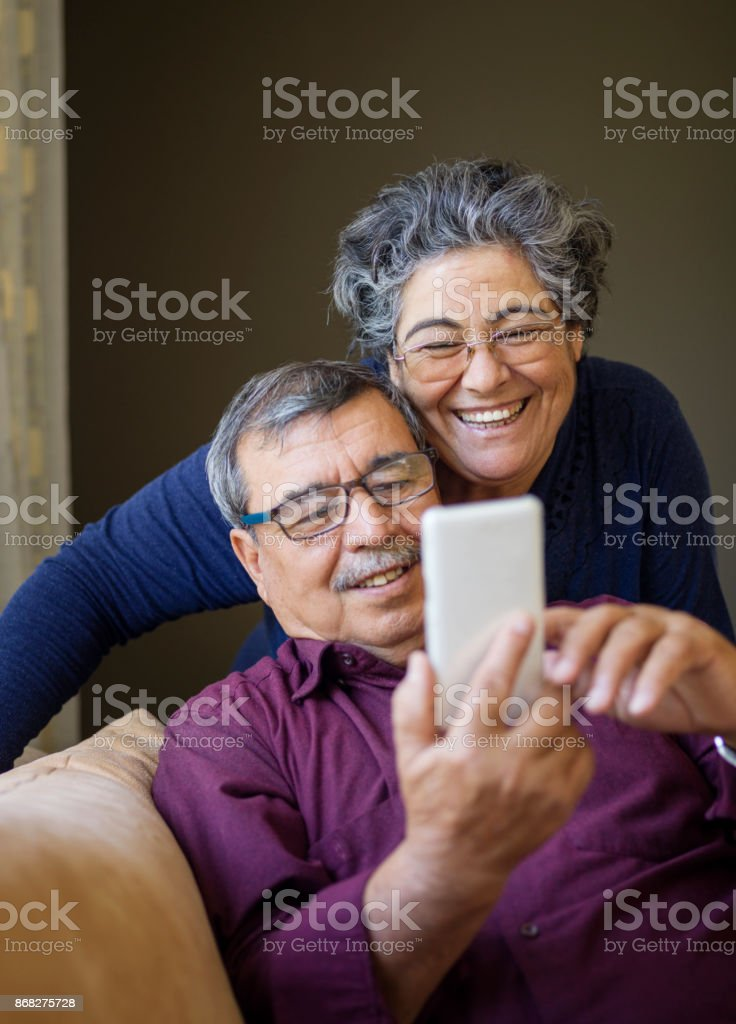 Senior couple using mobile phone stock photo