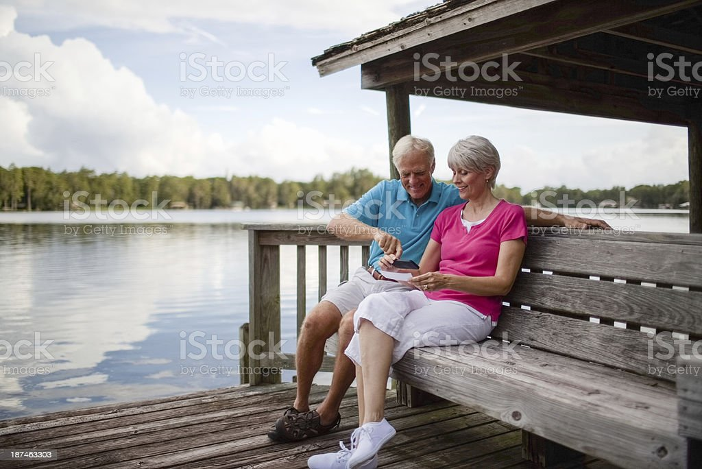 Senior Couple Using Mobile Phone To Deposit Bank Check stock photo