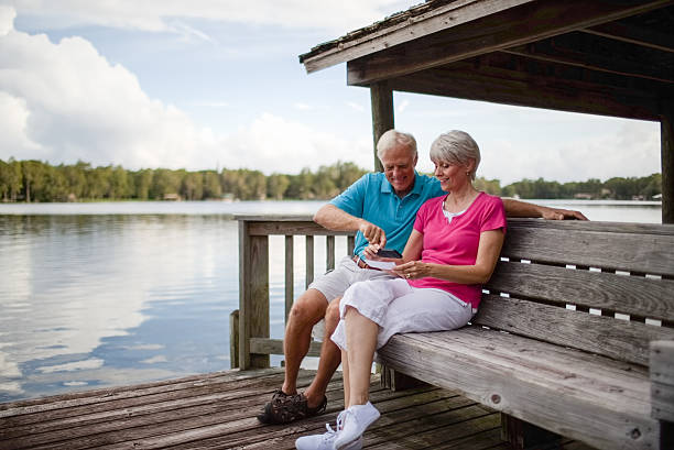 senior couple using mobile phone to deposit bank check - deposit slip stock photos and pictures