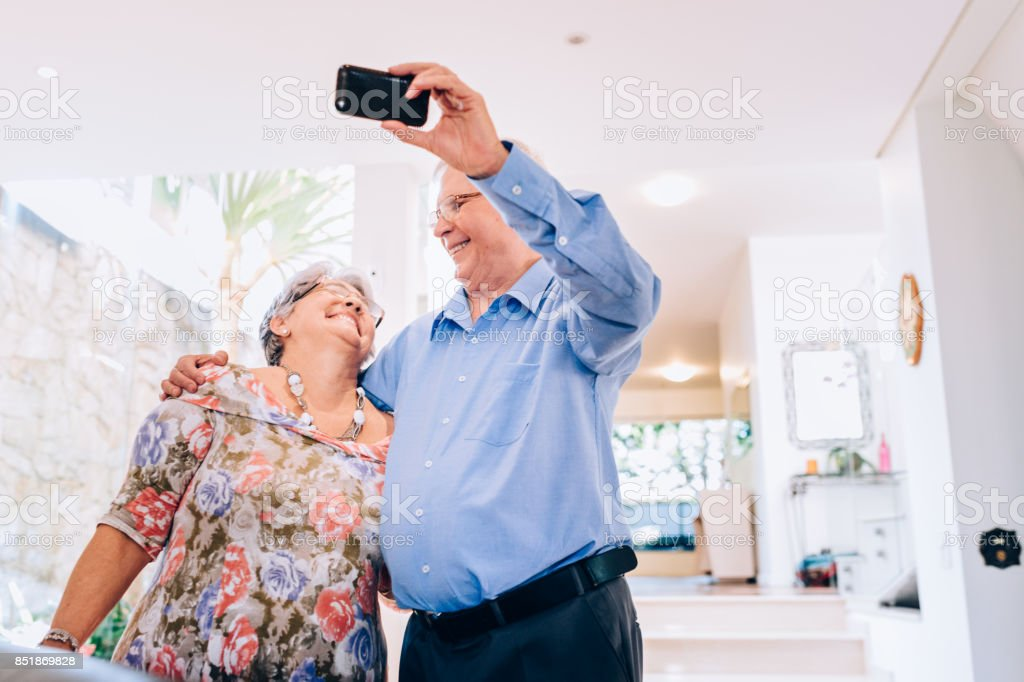 Senior couple using mobile phone to take a selfie at home stock photo