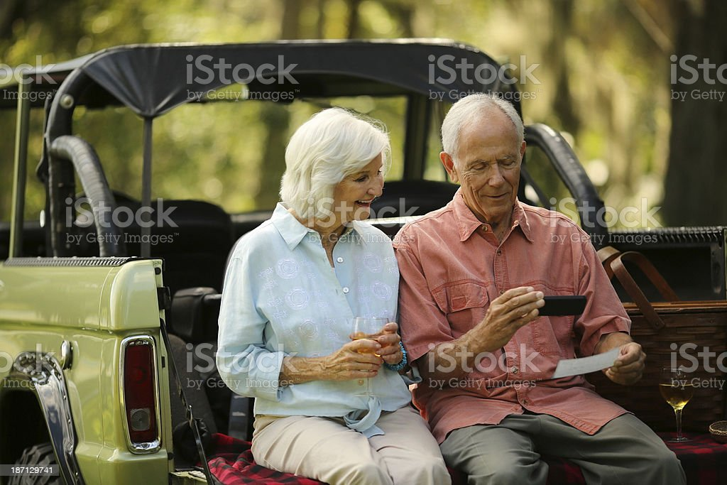 Senior Couple Using Smart Phone To Deposit Check In SUV stock photo