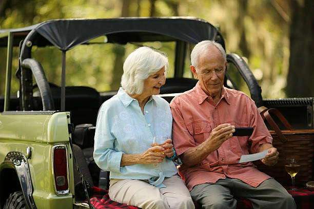 senior couple using smart phone to deposit check in suv - deposit slip stock photos and pictures