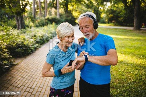 Senior couple using smart watch while exercising outdoors